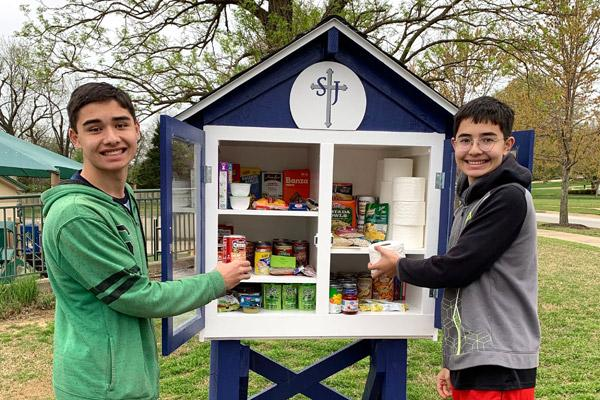 Spencer Katz (left) and his brother Riley Katz, both 14, smile after stocking the Little Free Pantry at St. Joseph Church in Fayetteville. A note was recently found taped to the pantry, thanking those who donate. (Judy Katz photo)