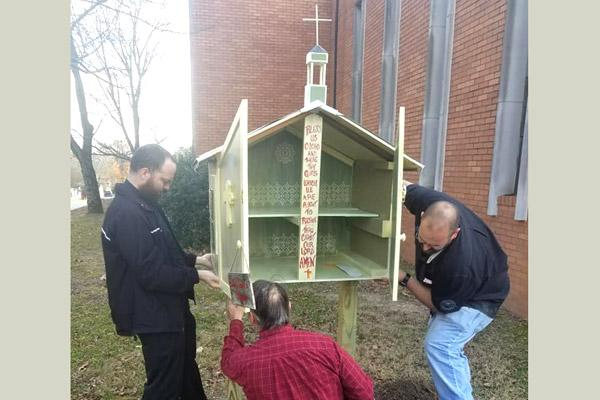 "Father Josh Stengel (left) and two parishioners work on getting the little church ""sharing box"" installed outside Our Lady of Good Counsel Church in Little Rock in November 2018. (File photo, courtesy Our Lady of Good Counsel Church)"