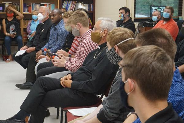 Bishop Anthony B. Taylor (center), vocations director Msgr. Scott Friend (left) and seminarians listen and pass around an Aunt Jemima syrup bottle as Father Warren Harvey discusses racism at the House of Formation in Little Rock July 2. (Aprille Hanson photo)