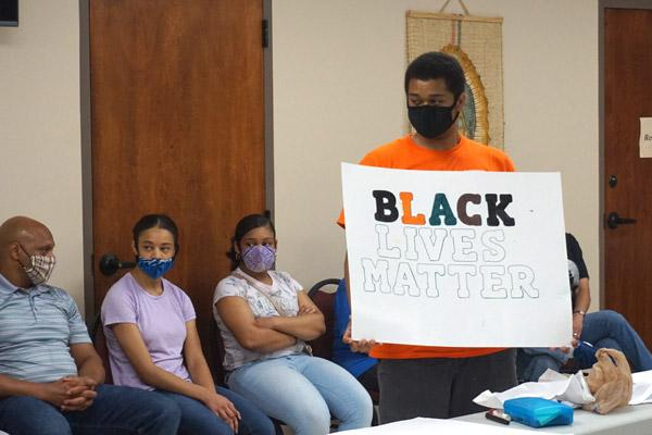 Caleb Hamilton, a parishioner at Immaculate Conception Church in North Little Rock, holds up a Black Lives Matter sign during the racism dialogue at the House of Formation in Little Rock. The Diocesan Council for Black Catholics discussed the true meanings of phrases like this. (Aprille Hanson photo)