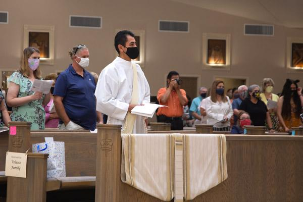 Father Daniel Velasco stands alone in his pew at Christ the King Church in Little Rock for his ordination. Customarily, family sits beside those being ordained. Because of the COVID-19 pandemic, Father Velasco's family could not travel from Mexico, but watched via livestream. (Bob Ocken photo)
