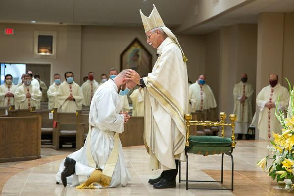 Bishop Anthony B. Taylor lays hands on Father Joseph Friend, a tradition to receive the strength of the Holy Spirit during his priestly ordination.