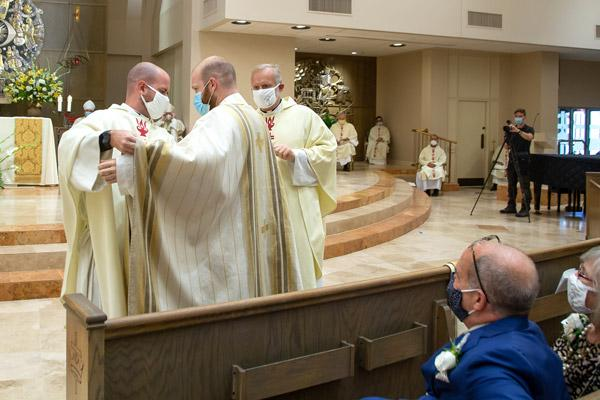 Father Joseph Friend was vested during his ordination Aug. 15 by his brother, Father Patrick Friend, ordained in 2018, and his uncle Msgr. Scott Friend, vocations director for the Diocese of Little Rock. (Bob Ocken photo)