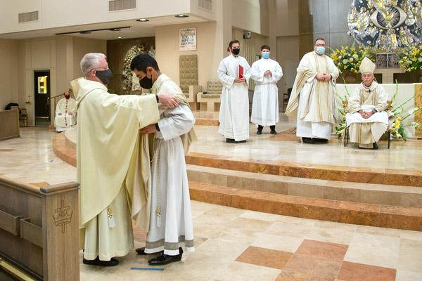 "Father Luke Turner, OSB, from St. Benedict Abbey in Atchison, Kan., vests Father Daniel Velasco during his ordination Aug. 15. The two met in seminary and are ""like brothers,"" Father Turner said. (Bob Ocken photo)"