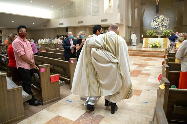 Father Daniel Velasco (left) and Father Joseph Friend embrace, returning to the altar for photos following their priestly ordination Mass Aug. 15. (Bob Ocken photo)