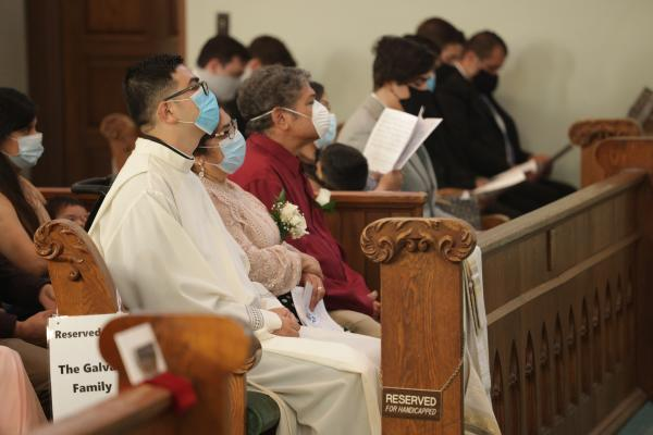 Deacon Omar Galván sits with family during his diaconate ordination Aug. 12 at Immaculate Conception Church in Fort Smith. (Travis McAfee photo)