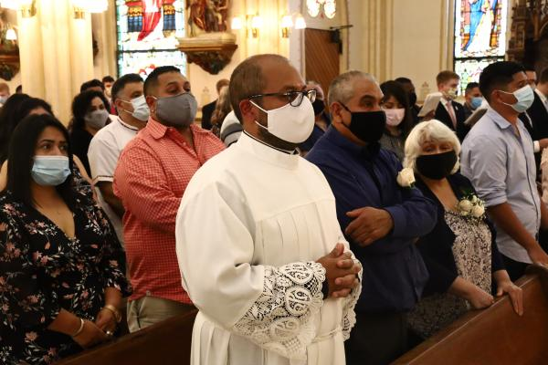 Emmanuel Torres stands in front of his large family during the opening of his diaconate ordination Mass, Aug. 13 at St. Edward Church in Little Rock. Torres is a native of North Little Rock. (Dwain Hebda photo)