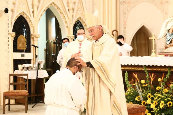 Bishop Anthony B. Taylor places his hands on seminarian Emmanuel Torres, ordaining him a transitional deacon. The ordination Mass was celebrated Aug. 13 at St. Edward Church in Little Rock. (Dwain Hebda photo)