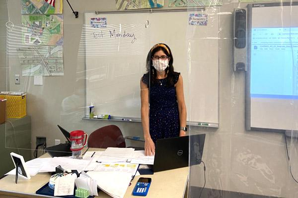 Catholic High School teacher Shannon Fratesi teaches a chemistry class behind plexiglass and a clear shower curtain. She has taken extra precautions due to having Multiple Sclerosis. (Father Patrick Friend photo)