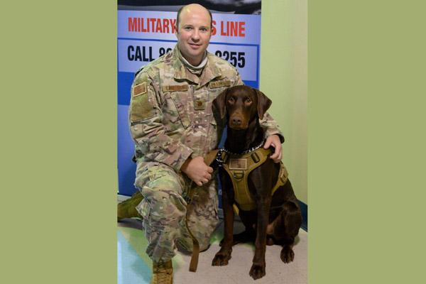 Father Matt Garrison smiles with Cletus, a certified therapy dog, at the Air National Guard base in Fort Smith in September to promote wellness and suicide prevention. Cletus has helped countless veterans struggling with PTSD. (Courtesy Father Matt Garrison)