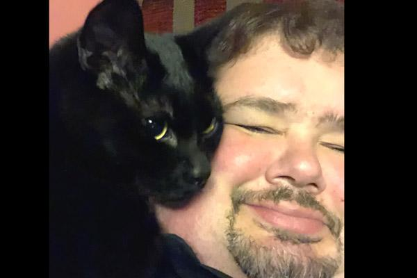 Father Shaun Wesley snuggles with his cat Jude Jan. 12. He adopted Jude and Maxine, both black cats, for companionship and so fur wouldn't show on his clerics. (Courtesy Father Shaun Wesley)
