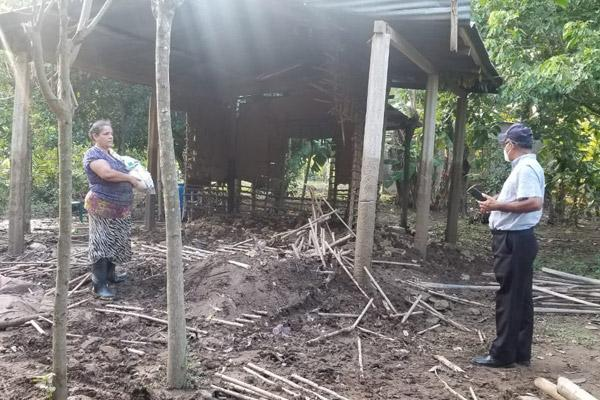 Father Gildo Ramírez, with the Diocese of Trujillo, speaks with a woman Nov. 12 by a structure that was destroyed. Flooding from two hurricanes in the space of two weeks -- Eta and Iota -- washed away houses, roads and bridges. (Courtesy Father Gildo Ramírez)