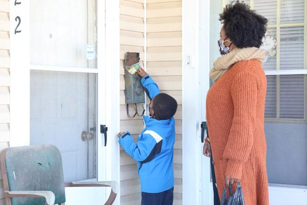 Dominic Mitchell, 3, leaves candy in a neighbor's mailbox, assisted by his mother, Dionne Mitchell, during the march in honor of Dr. Martin Luther King Jr., hosted Jan 17 by St. Augustine Church in North Little Rock. (Dwain Hebda photo)